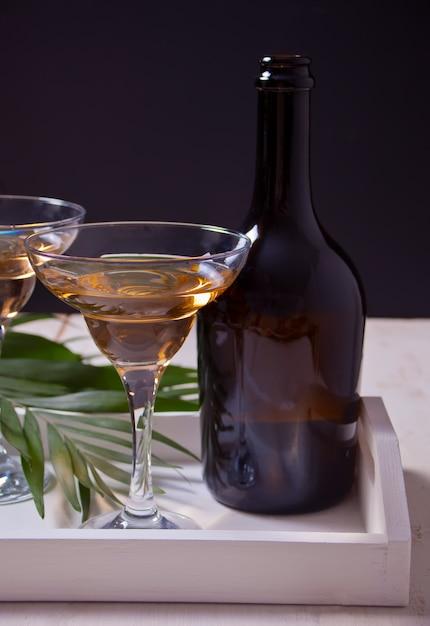 Vinho branco em um óculos, garrafa na bandeja de madeira branca. Foto Premium
