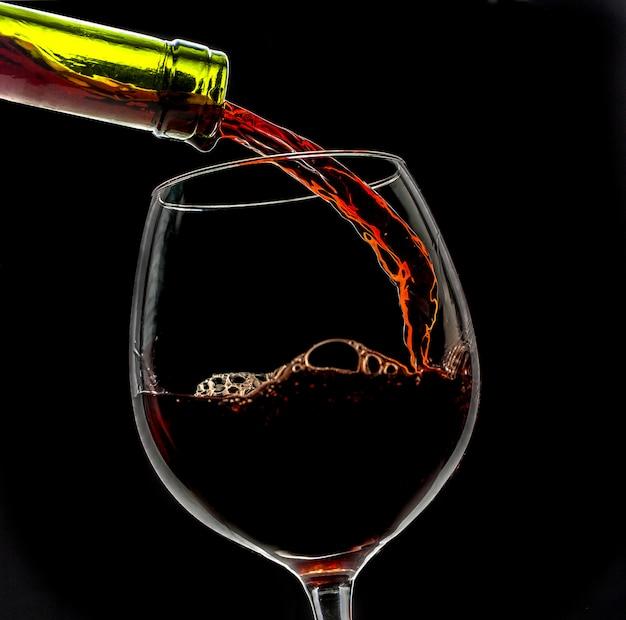 Vinho de uva derramado em copo de vinho sobre fundo preto Foto Premium