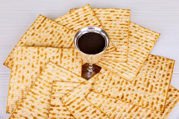 Vinho kosher vermelho com um prato branco de matzah ou matza e uma hagadá de páscoa Foto Premium