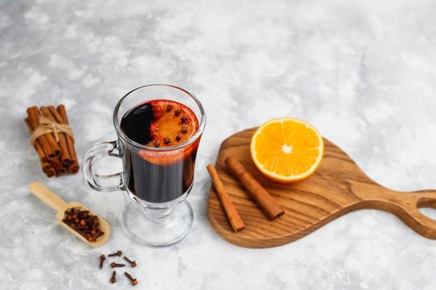 Vinho quente com glintwine servido em copos para mesa de natal com laranja e especiarias Foto gratuita