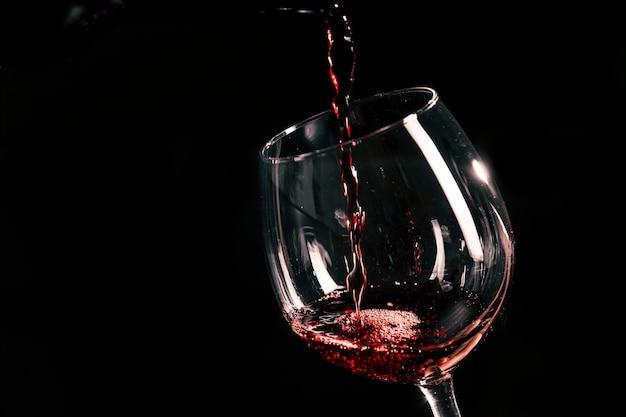 Vinho tinto derramando em vidro Foto Premium