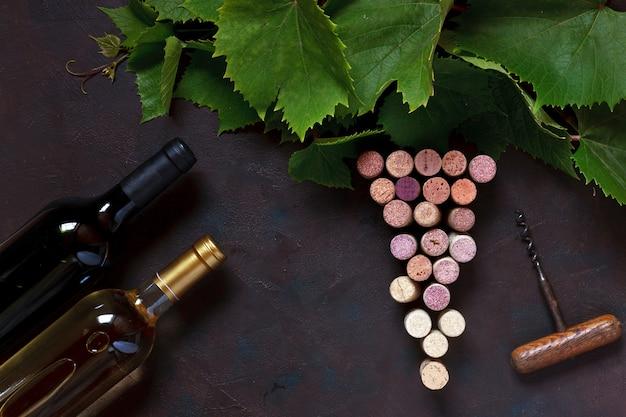 Vinho tinto e branco em garrafas, rolhas, saca-rolhas e folhas de uva. Foto Premium