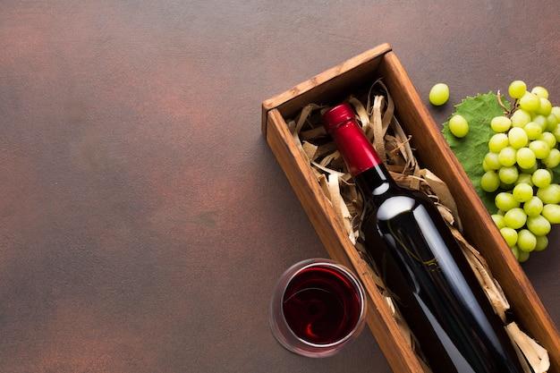 Vinho tinto em uma caixa e uvas brancas Foto gratuita
