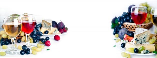Vinho, uva e queijo sobre branco Foto Premium