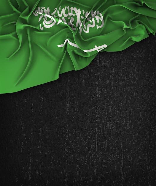 Vintage da bandeira de arábia saudita em um quadro preto do grunge com espaço para o texto Foto Premium
