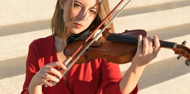 Violinista feminina tocando música no violino Foto gratuita
