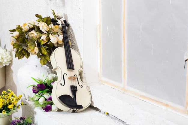 Violino branco com flores e quarto branco Foto Premium