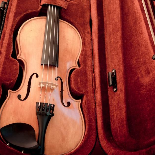 Violino e arco em estojo vermelho escuro. Foto Premium