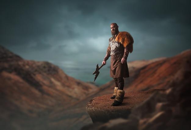 Viquingue bonito com machado, vestido com roupas nórdicas tradicionais, em pé no topo de uma montanha rochosa. antigo guerreiro escandinavo Foto Premium