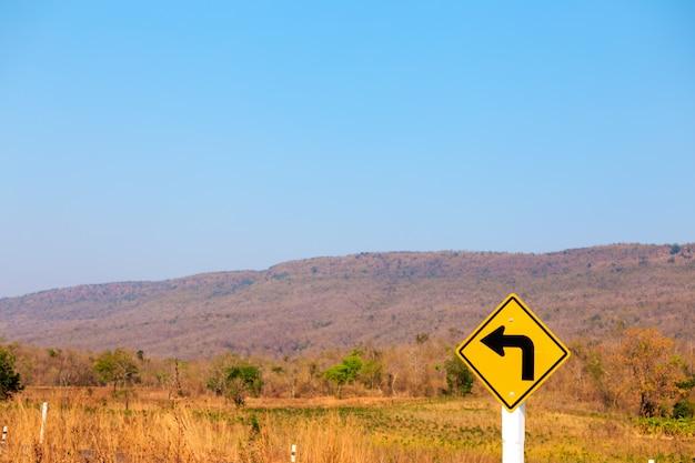 Vire à esquerda, sinal de trânsito na estrada Foto Premium