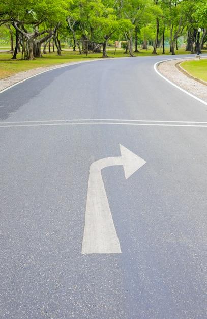 Vire a seta para a direita e curvy road of fresh green Foto Premium