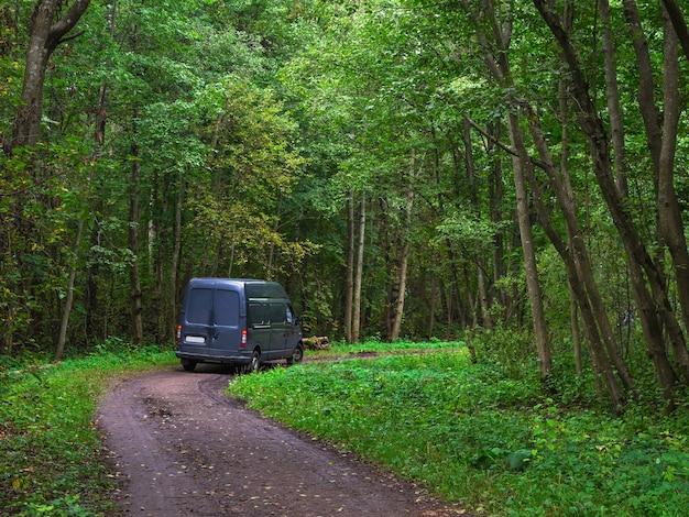 Vire em uma bela estrada florestal. um caminhão entra em uma estrada florestal verde. Foto Premium