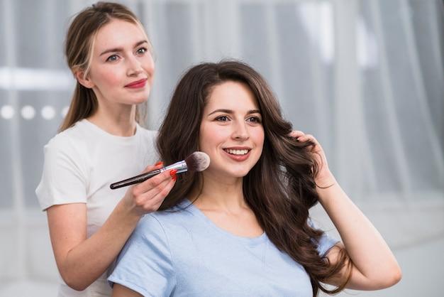 Visagiste feminina fazendo maquiagem Foto gratuita