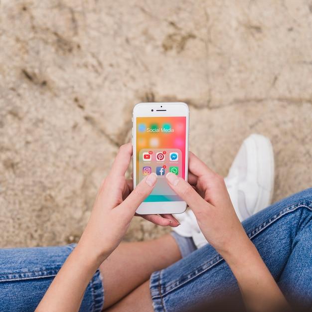 Visão aérea da mão de uma mulher usando o celular com notificações na tela Foto gratuita