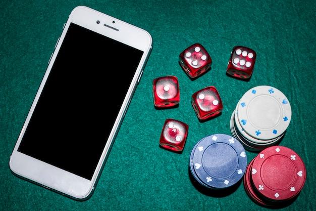 Visão aérea da mesa de poker com dadinhos vermelhos; fichas de casino e smartphone Foto gratuita