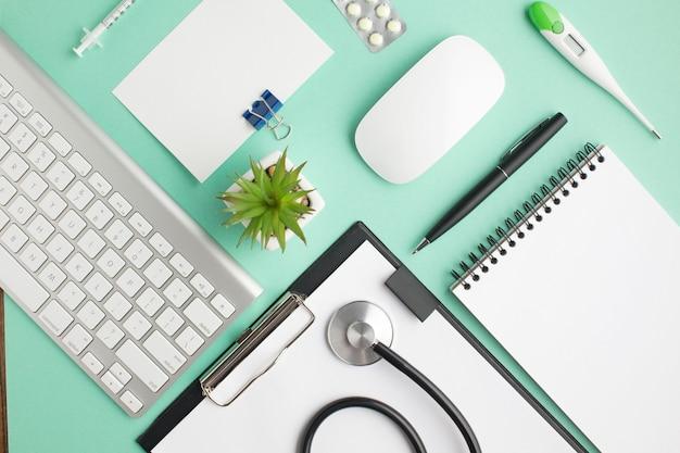 Visão aérea da mesa do médico com pílulas e material de escritório Foto gratuita