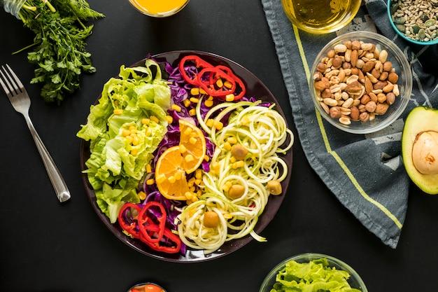 Visão aérea da salada saudável guarnecida no prato com trações e garfo contra fundo preto Foto gratuita