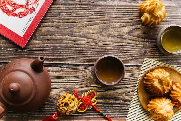 Visão aérea, de, argila, bule, e, teacups, com, caseiro, coco, biscoitos, sobre, a, tabela madeira Foto gratuita