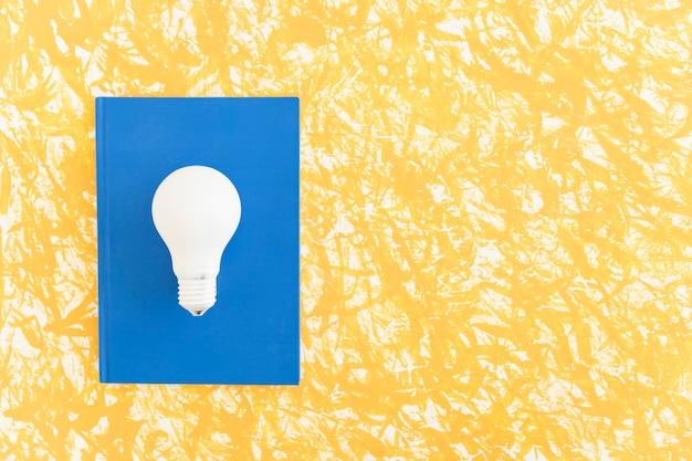 Visão aérea, de, bulbo branco leve, ligado, azul, caderno, sobre, a, padrão, fundo Foto gratuita