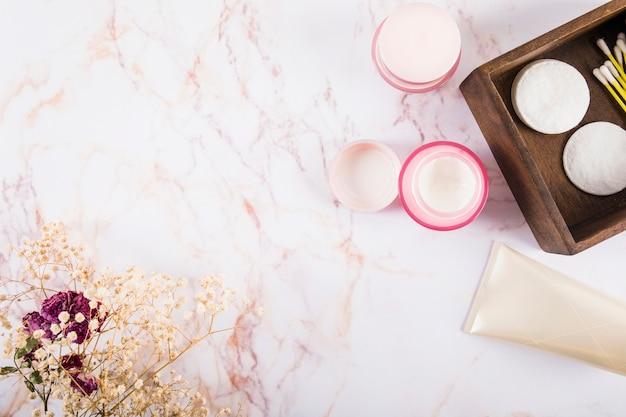 Visão aérea de creme hidratante e flores em mármore Foto gratuita