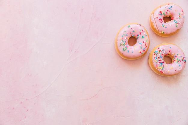 Visão aérea de donuts frescos com chuviscos em pano de fundo rosa Foto gratuita