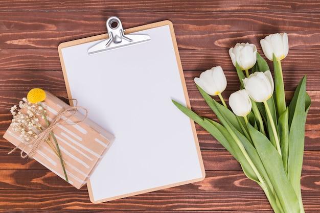 Visão aérea de flores tulipa branca; papel em branco; área de transferência e caixa de presente sobre a mesa de madeira Foto gratuita