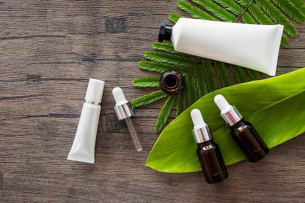 Visão aérea de garrafas de óleo essencial e tubo branco cosmético em folhas verdes sobre a mesa de madeira Foto gratuita