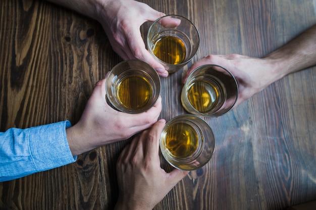 Visão aérea de mãos segurando copos de bebidas na mesa Foto gratuita