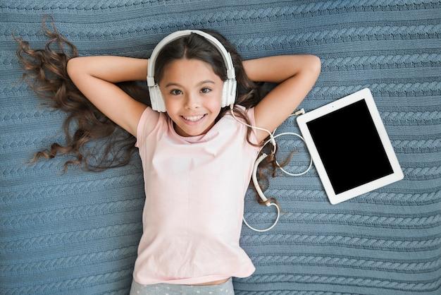 Visão aérea, de, menina sorridente, escutar música, ligado, headphone, anexado, para, tablete digital Foto gratuita