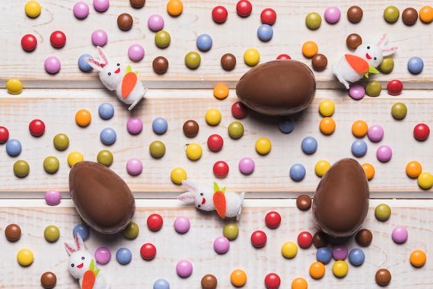 Visão aérea, de, ovos páscoa, e, coelhões, sobre, a, coloridos, jóia, bala doce, ligado, escrivaninha madeira Foto gratuita