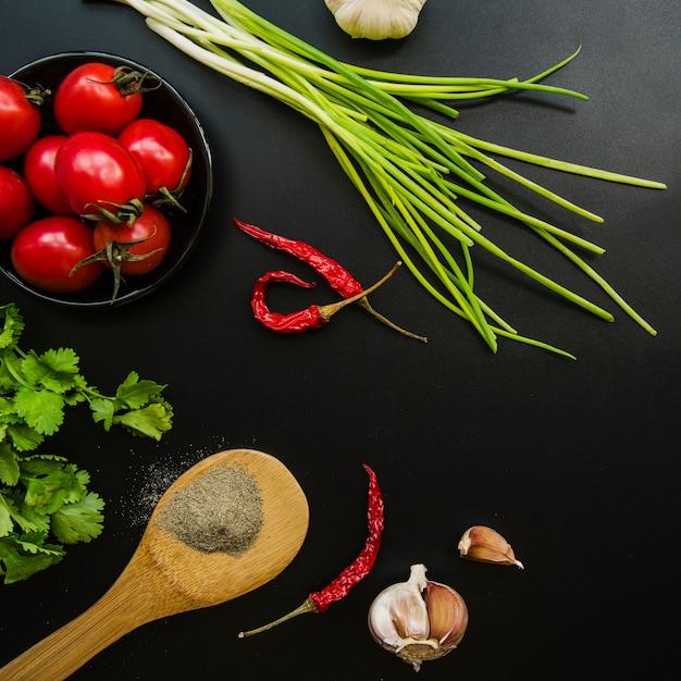 Visão aérea de tomate; pimentões vermelhos; cebolinha; alho; salsa e especiarias sobre fundo preto Foto gratuita