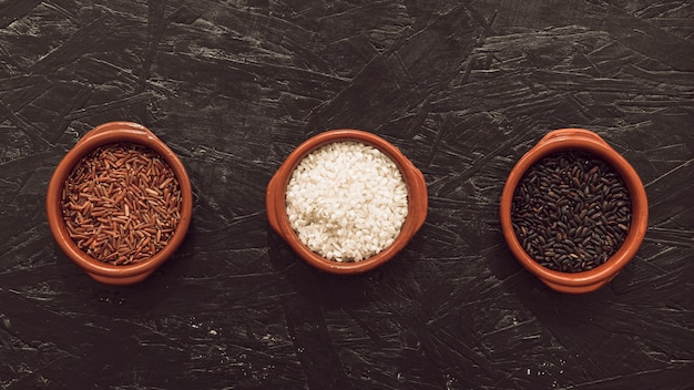 Visão aérea, de, três, orgânica, arroz, grão, tigela, ligado, áspero, textured, fundo Foto gratuita