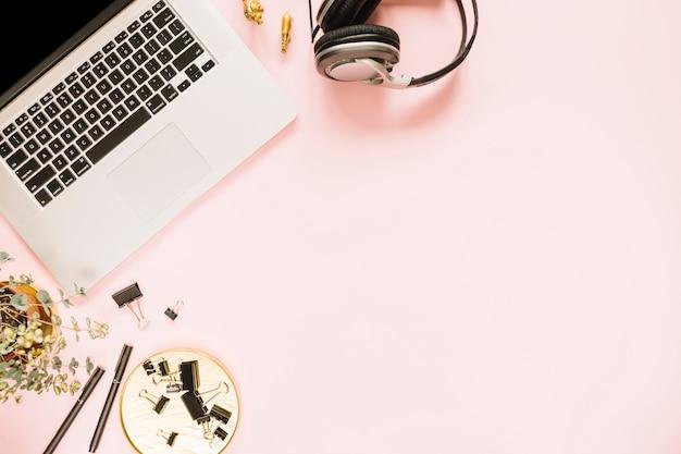 Visão aérea de um laptop aberto no pano de fundo rosa Foto gratuita