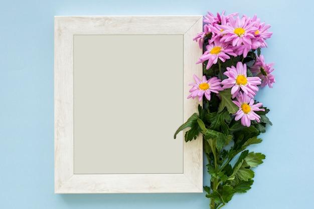 Visão aérea, de, um, margarida roxa, margarida, flores, e, branca, frame de retrato, ligado, azul, fundo Foto gratuita