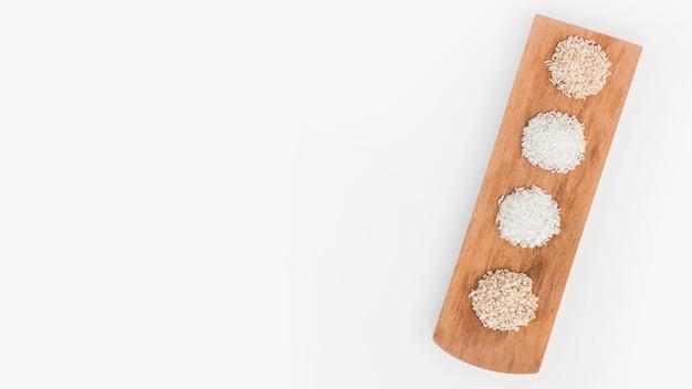 Visão aérea de vários arroz na bandeja de madeira sobre a superfície branca Foto gratuita