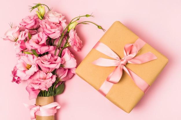 Visão aérea do buquê de flores frescas e caixa de presente decorativo embrulhado Foto gratuita