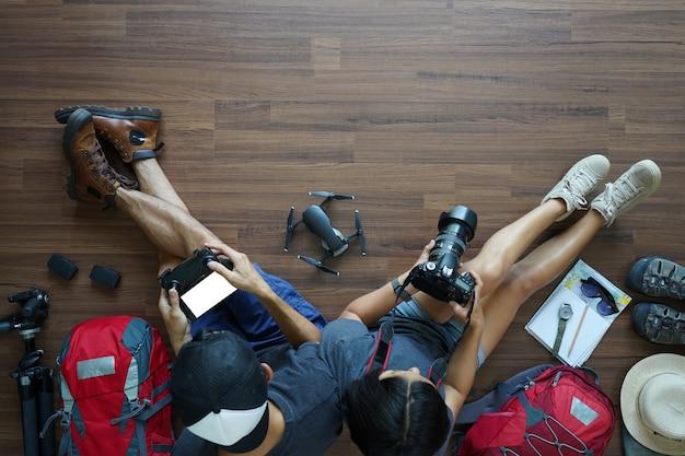 Visão aérea do casal jovem do viajante planejamento com segurando a câmera com drone Foto Premium