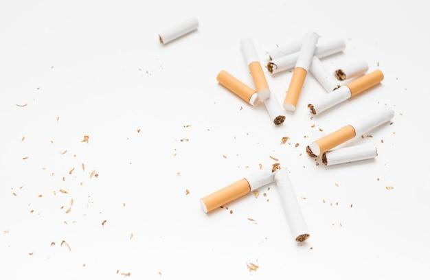 Visão aérea do cigarro quebrado e tabaco contra o pano de fundo branco Foto gratuita