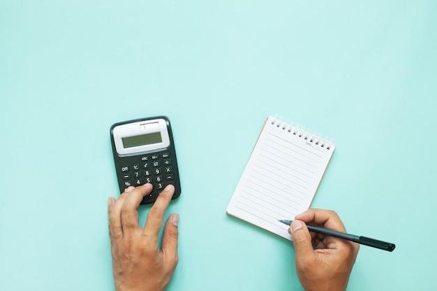 Visão aérea do homem mãos usando calculadora e papel de nota sobre fundo de cor azul com espaço de cópia Foto Premium