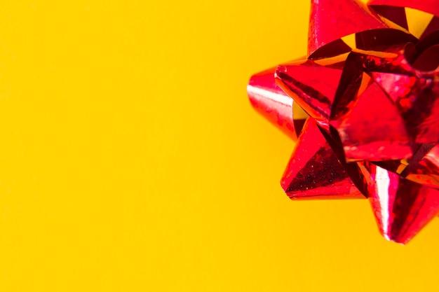 Visão aérea do laço de fita vermelha em fundo amarelo Foto gratuita