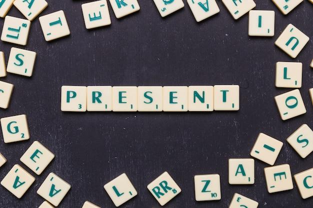Visão aérea do presente texto em letras scrabble sobre pano de fundo preto Foto gratuita