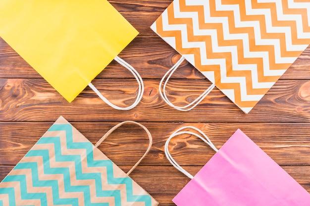 Visão aérea do saco de papel decorativo na mesa de madeira Foto gratuita