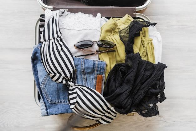 Visão aérea do saco do viajante aberto com roupas e acessórios Foto gratuita