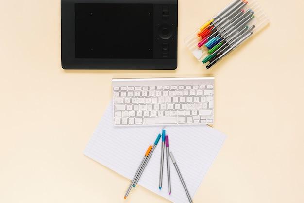 Visão aérea do tablet digital gráfico com teclado e canetas de feltro no caderno sobre o fundo bege Foto gratuita