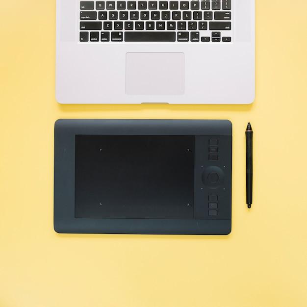 Visão aérea do tablet digital gráfico e laptop na superfície amarela Foto gratuita