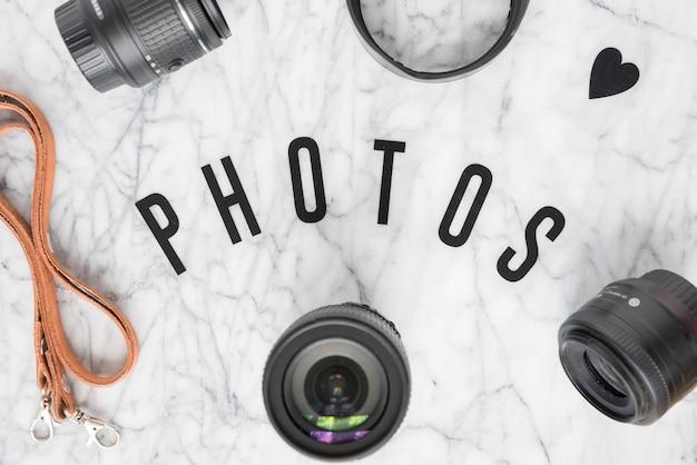Visão aérea do texto de fotos cercado com acessórios de câmera e heartshape sobre fundo de mármore Foto gratuita