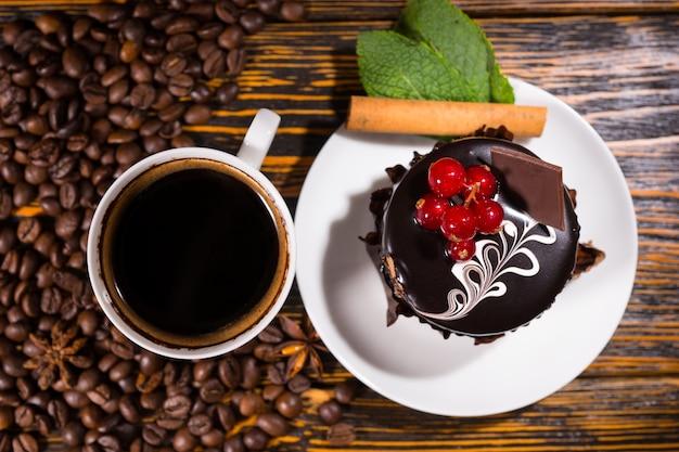 Visão aérea dos grãos de café ao lado da sobremesa Foto Premium