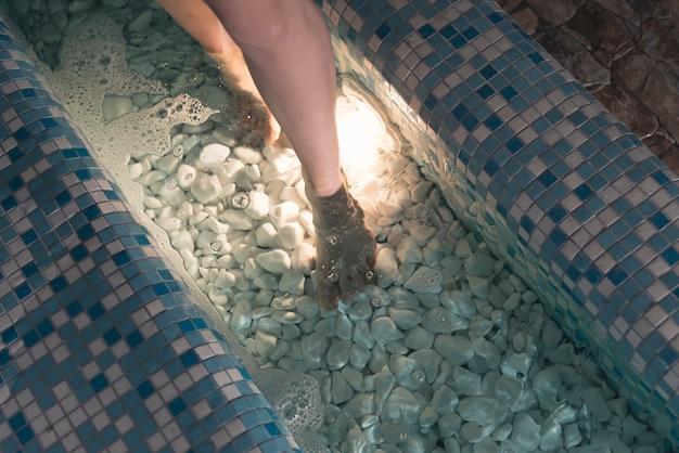 Visão aérea dos pés da mulher na banheira Foto gratuita
