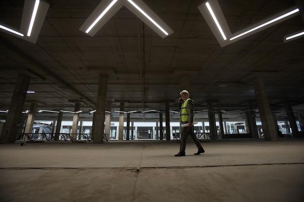 Visão de grande angular de um empresário maduro usando capacete de segurança e falando ao telefone enquanto caminha pelo canteiro de obras dentro Foto Premium
