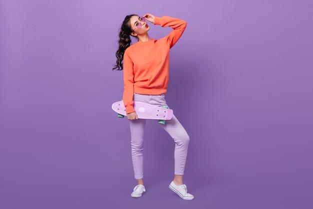Visão do comprimento total da menina coreana na moda com skate. foto de estúdio de linda mulher asiática segurando longboard no fundo roxo. Foto gratuita
